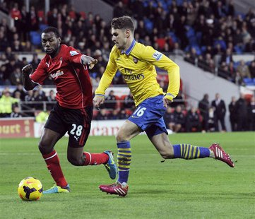 Cardiff City's Kevin Theophile-Catherine (L) challenges Arsenal's Aaron Ramsey during their English Premier League soccer match at Cardiff C