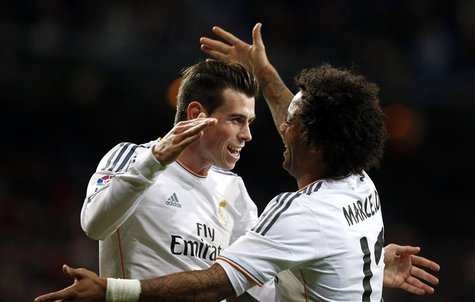 Real Madrid's Gareth Bale (L) celebrates his goal against Real Valladolid with teammate Marcelo during their Spanish First Division soccer m