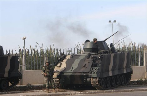 Lebanese army soldiers stand by a tank while monitoring a street in Tripoli, northern Lebanon, November 30, 2013. REUTERS/Stringer