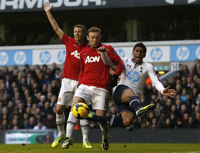 Tottenham Hotspur's Paulinho (R) challenges Manchester United's Wayne Rooney during their English Premier League soccer match at White Hart