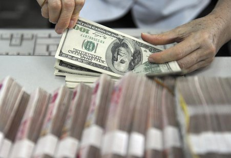 A clerk counts U.S. dollar banknotes after counting Chinese 100 Yuan banknotes at a branch of the Agricultural Bank of China in Qionghai, Ch