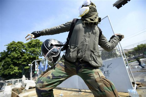 An anti-government protester throws a rock at Thai riot police as they attempt to remove barricades outside Government House in Bangkok Dece
