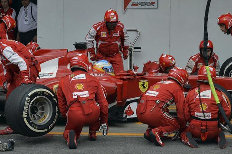 Ferrari Formula One driver Fernando Alonso of Spain is attended to by his crew during a pit stop during the Brazilian F1 Grand Prix at the I