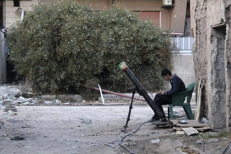 A Free Syrian Army fighter listens to music as he sits beside a rocket launcher, on a damaged street in the Jobar neighbourhood of Damascus