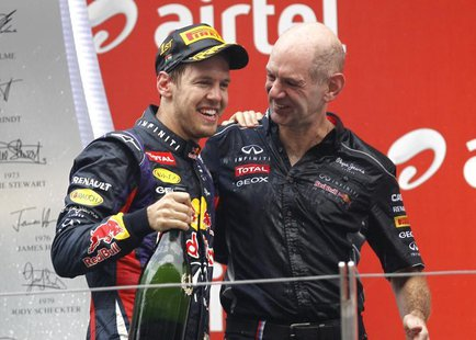 Red Bull Formula One driver Sebastian Vettel of Germany (L) celebrates on the podium with Red Bull technical chief Adrian Newey after winnin