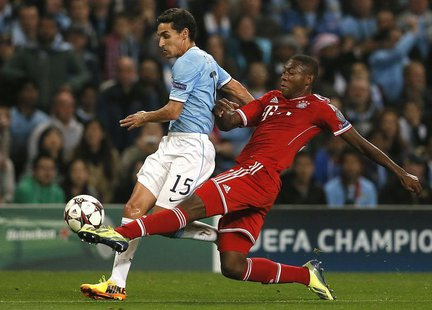 Manchester City's Jesus Navas (L) challenged by Bayern Munich's David Alaba during their Champions League soccer match at the Etihad Stadium