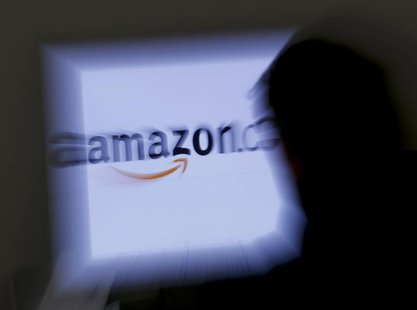A zoomed illustration image of a man looking at a computer monitor showing the logo of Amazon is seen in Vienna November 26, 2012. To match