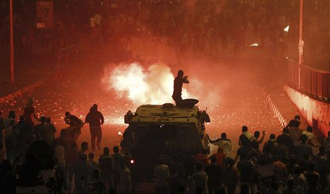 A riot police officer, on a armoured personnel carrier surrounded by anti-Mursi protesters (foreground), fires rubber bullets at members of