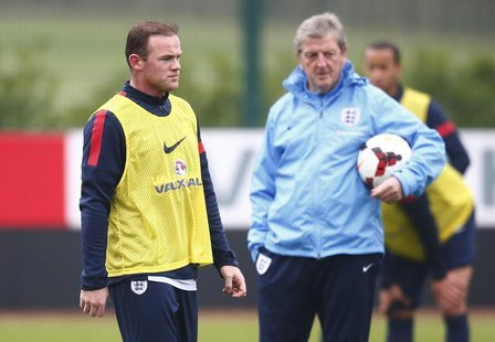 England national team soccer player Wayne Rooney (L) walks past manager Roy Hodgson during a team training session at Arsenal's training fac