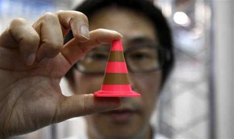 A staff of Nihonbinary shows an Acrylonitrile butadiene styrene pylon which is printed by the 3D printer MakerBot Replicator 2X during the I