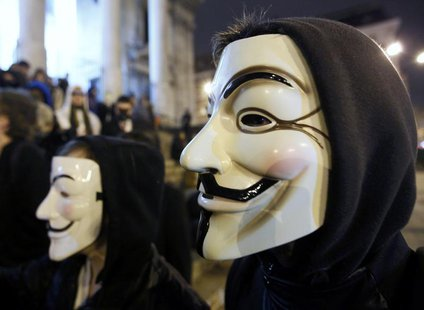 "A protester wearing a Guy Fawkes mask, symbolic of the hacktivist group ""Anonymous"", takes part in a protest in central Brussels January 28,"