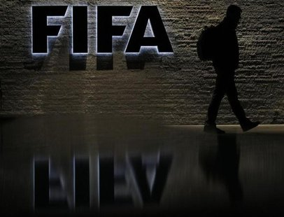 A man is silhouetted as he makes his way past the main entrance of FIFA headquarters, the Home of FIFA, in Zurich October 20, 2010. REUTERS/