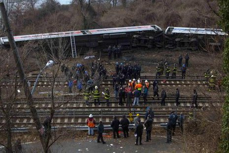 Emergency workers stand at the site of a Metro-North train derailment in the Bronx borough of New York December 1, 2013.  CREDIT: REUTERS/ERIC THAYER