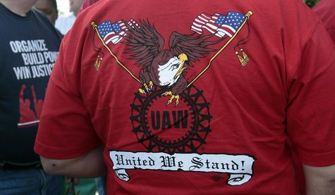 A United Auto Workers union member wears a shirt with 'UAW United We Stand' on it during a ceremony where members of UAW Local 600 unfurled
