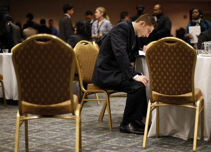A job seeker fills out forms at a table while attending a career fair with prospective employers in New York City, October 24, 2012. REUTERS