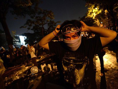 Anti-government protesters take cover from tear gas as they attack Government House during demonstrations in Bangkok December 2, 2013. REUTE