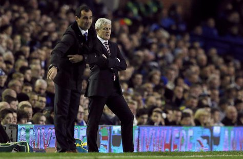 Everton's manager Roberto Martinez (L) gestures as his Stoke City counterpart Mark Hughes looks on during their English Premier League socce
