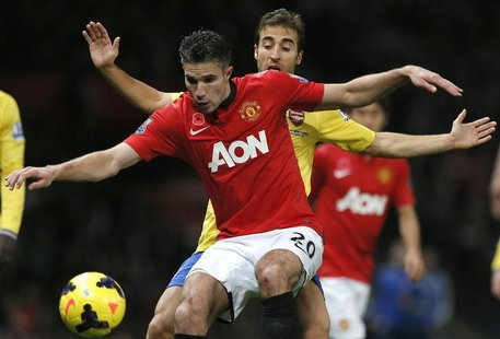 Arsenal's Mathieu Flamini challenges Manchester United's Robin van Persie (L) during their English Premier League soccer match at Old Traffo