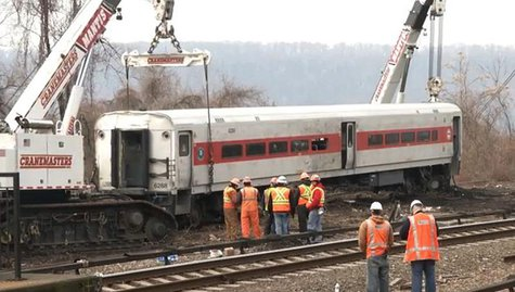 Heavy cranes lift a derailed Metro-North train car back onto the tracks in New York, in this still image from video taken by the National Tr