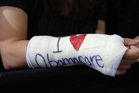 "Cathey Park of Cambridge, Massachusetts wears a cast for her broken wrist with ""I Love Obamacare"" written upon it prior to U.S. President Ba"