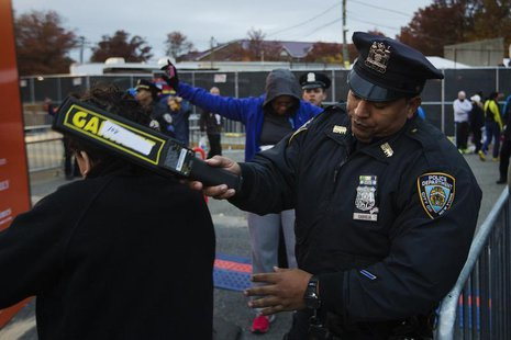 New York Police Department officers perform a security sweep on runners arriving to take part in the New York City Marathon, November 3, 201