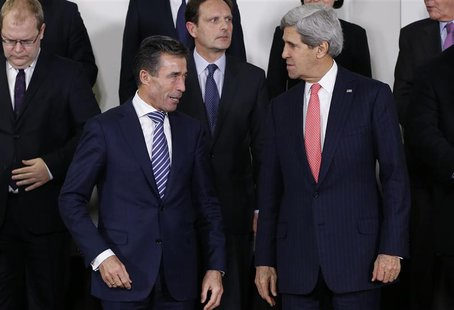 NATO Secretary General Anders Fogh Rasmussen and U.S. Secretary of State John Kerry (R) pose for a family photo during a NATO foreign minist
