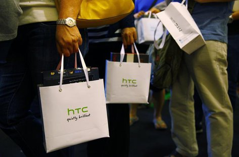 Customers hold bags containing their HTC One mobile phone purchases during the first day of public sales at Taman Anggrek Mall in Jakarta, J