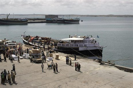 Workers stand at the sea port of the coastal town of Kismayu in southern Somalia in this November 12, 2013 file photo. REUTERS/Siegfried Mod