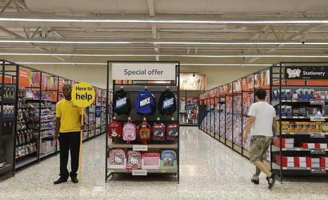 A customer service representative stands in an aisle at a Tesco Extra supermarket in Watford, north of London August 8, 2013. REUTERS/Suzann
