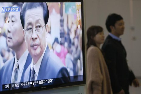 A couple walks past a television showing a report on Jang Song Thaek, North Korean leaders' uncle, at a railway station in Seoul December 3,
