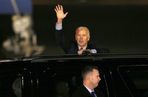 U.S. Vice President Joseph Biden waves from his van upon his arrival at Haneda airport in Tokyo December 2, 2013. REUTERS/Issei Kato