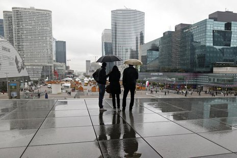 People are silhouetted as they shelter from rain under the Arche de la Defense, in the financial district west of Paris, November 8, 2013. R
