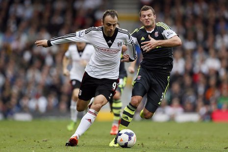 Fulham's Dimitar Berbatov (L) challenges Stoke City's Erik Pieters during their English Premier League soccer match at Craven Cottage in Lon