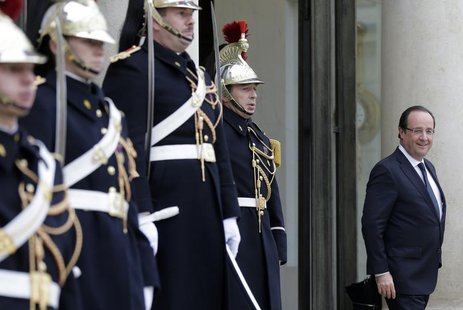 French President Francois Hollande (R) waits for a guest on the steps of the Elysee Palace in Paris December 4, 2013. REUTERS/Jacky Naegelen