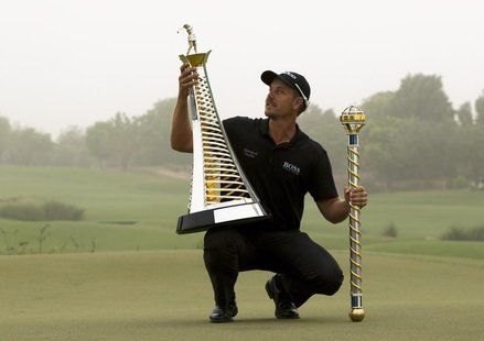 Henrik Stenson of Sweden poses with his trophies after winning the DP World Tour Championship in Dubai November 17, 2013. REUTERS/Caren Firo