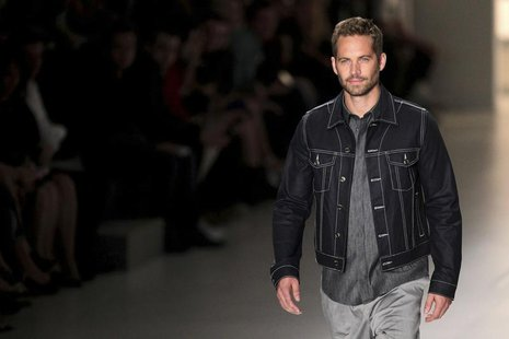 U.S. actor Paul Walker presents a creation from Colcci's 2013/2014 summer collection during Sao Paulo Fashion Week March 21, 2013. REUTERS/F