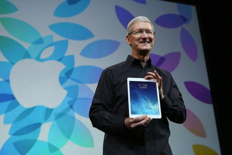 Apple Inc CEO Tim Cook holds up the new iPad Air during an Apple event in San Francisco, California October 22, 2013. REUTERS/Robert Galbrai