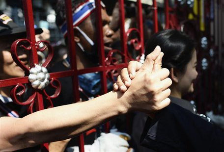 An anti-government protester touches the hand of a police officer through the main gate of the Thai Police Headquarters in Bangkok December