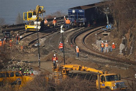 Workers are seen on the tracks of the Metro-North train derailment in the Bronx borough of New York December 3, 2013. REUTERS/Shannon Staple