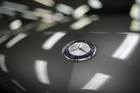 A company logo is seen on a Mercedes-Benz A-class car displayed in a dealership of German car manufacturer Daimler in Paris, July 30, 2013.