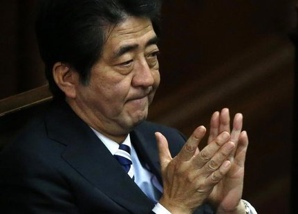 Japan's Prime Minister Shinzo Abe claps his hands during the Lower House plenary session of the parliament in Tokyo November 26, 2013. REUTE