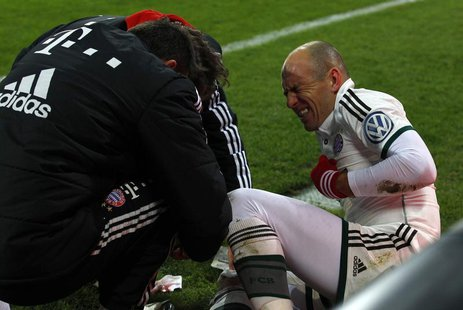 Bayern Munich's Arjen Robben reacts as medical assistants attend to his leg during the team's third round German soccer cup (DFB-Pokal) matc