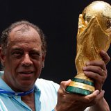 Former Brazilian soccer captain Carlos Alberto Torres holds the 2014 FIFA World Cup Brazil trophy during its unveiling ceremony at a Soccere