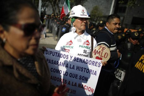 A demonstrator holds a placard while arriving to a protest against the energy reform outside the Senate building in Mexico City December 4,