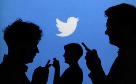 People holding mobile phones are silhouetted against a backdrop projected with the Twitter logo in this illustration picture taken in Warsaw