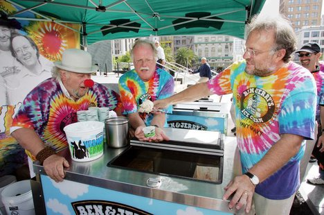 As iconic 1960's activist Wavy Gravy (L) looks on, Ben & Jerry's Ice Cream co-founders Ben Cohen (C) and Jerry Greenfield serve the first sc