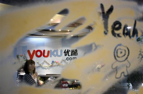 An employee is seen through a glass wall as she walks past the logo of Youku.com above the reception desk at the company's headquarters in B