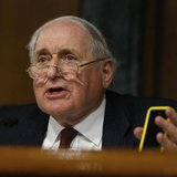Senate homeland security and governmental affairs investigations subcommittee Chairman Carl Levin (D-MI) holds an iPhone as he speaks to App