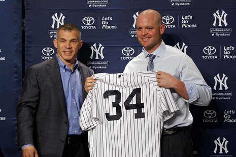 Dec 5, 2013; Bronx, NY, USA; New York Yankees manager Joe Girardi (right) and new catcher Brian McCann during press conference at Yankees St