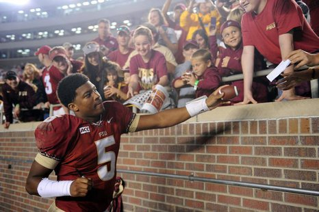 Nov 23, 2013; Tallahassee, FL, USA; Florida State Seminoles quarterback Jameis Winston (5) signs autographs for fans after the game against